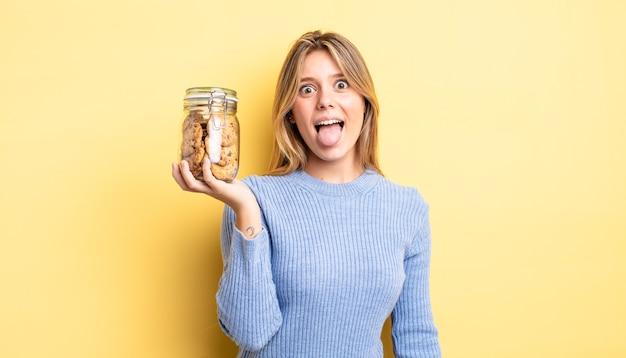 Mooie blonde meid met vrolijke en rebelse houding, grappen maken en tong uitsteken. zelfgemaakte koekjes concept
