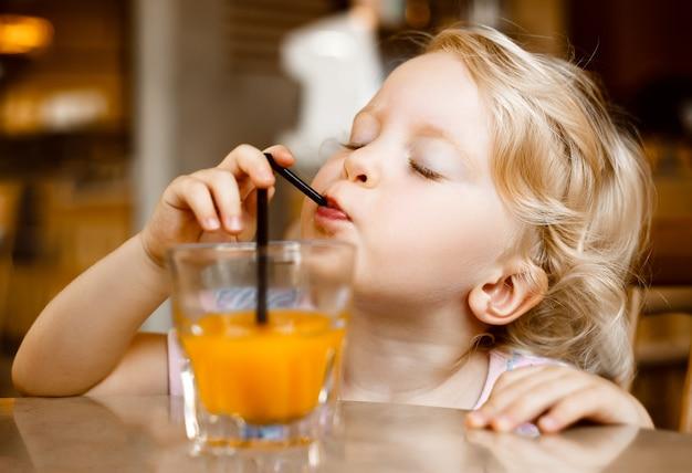 Mooie blonde meid zit aan tafel in het café buiten sap te drinken en desserts te eten