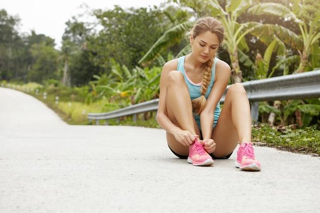 Mooie blonde meisje atleet in sportkleding en roze sneakers veters koppelverkoop terwijl het hebben van pauze tijdens het hardlopen van training, zittend op weg tegen groen bos met tropische bomen