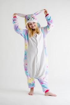 Mooie blonde meisje die zich voordeed op wit in kigurumi pyjama's, bunny kostuum