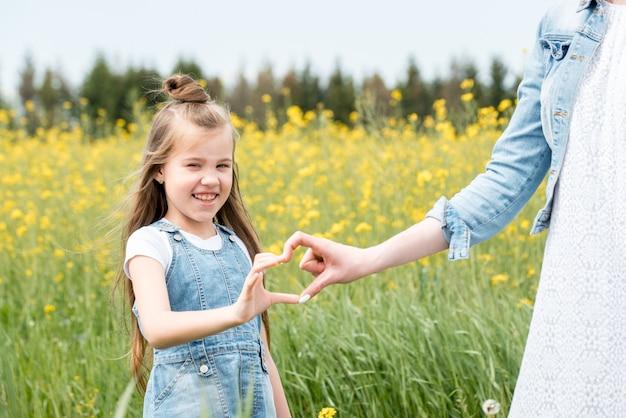 Mooie blonde meisje in een bloeiende veld van koolzaad. gele bloemen, in handen chamomiles snoep op stok, moeder met dochter, moederlijke liefde zomerdag in dorp. vrijheid, lucht is de wind.