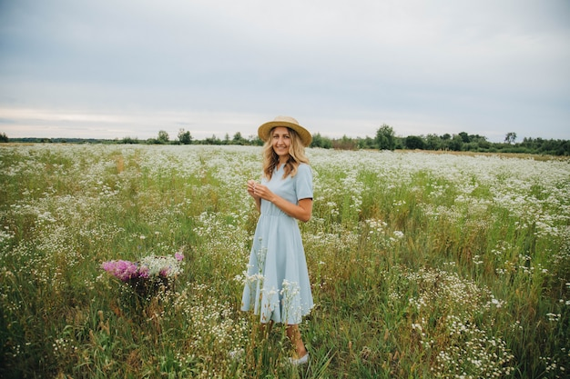 Mooie blonde meisje in een veld van madeliefjes. vrouw in een blauwe jurk in een veld van witte bloemen. meisje met een boeket van madeliefjes. zomer tedere foto in het dorp. wilde bloemen. meisje in een strooien hoed