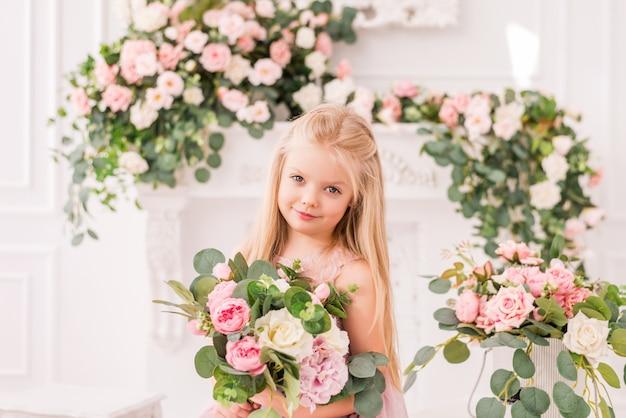 Mooie blonde meisje in een zachte paarse jurk op een achtergrond van bloemen poseren. schattige baby model in de afbeelding van een prinses, ze draagt een volledige lila jurk