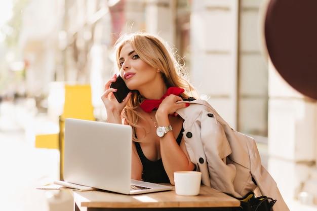 Mooie blonde meisje in polshorloge praten over de telefoon tijdens het werken met laptop in café