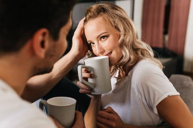 Mooie blonde meisje verliefd kijken naar haar vriendje en koffie drinken uit de beker. inschrijving schattig portret van romantisch koppel thuis.