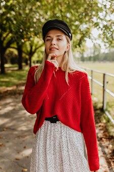 Mooie blonde met natuurlijke make-up die er teder uitziet. mooi model in mooie jurk poseren op het bospad.