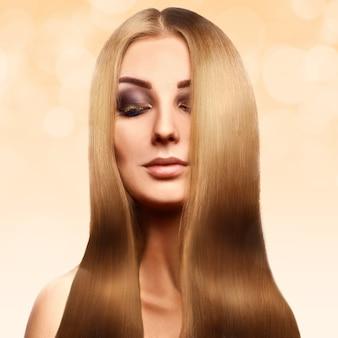 Mooie blonde met perfect gezond lang haar met professionele make-up op abstract geel