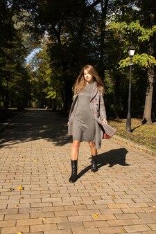 Mooie blonde model met lang haar in gebreide jurk en warme jas wandelen in het park op zonnige dag