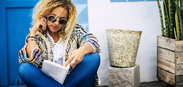 Mooie blonde model volwassen vrouw geniet van het boek dat buiten leest met blauwe deur en wit huis