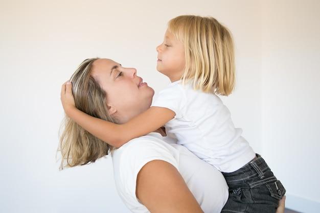 Mooie blonde moeder die dochter houdt en haar bekijkt