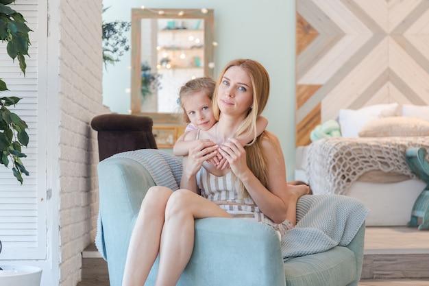 Mooie blonde moeder en schattig dochtertje met plezier en spelen in een modieuze flat met een stijlvol design