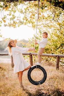 Mooie blonde moeder in een witte jurk en zoon rijden een band op een boom en lachen.