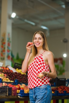 Mooie blonde poseren met perziken op de markt
