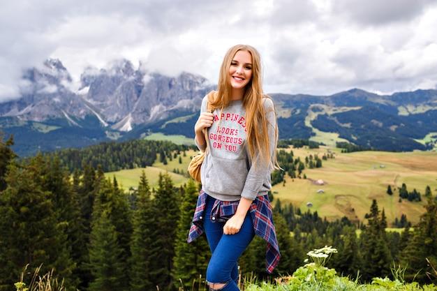 Mooie blonde reizigersvrouw bij bergen. avontuur, alleen reizen