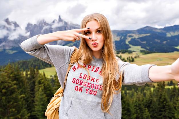 Mooie blonde reizigersvrouw die pret heeft bij bergen.