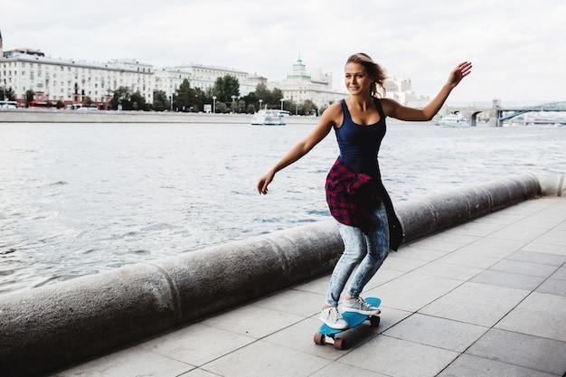 Mooie blonde skateboard op de promenade