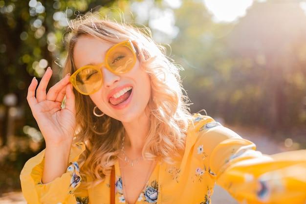Mooie blonde stijlvolle lachende vrouw met grappige gezichtsuitdrukking in gele blouse dragen van een zonnebril selfie foto maken