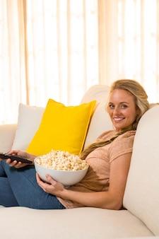 Mooie blonde tv kijken en popcorn zittend op de bank eten