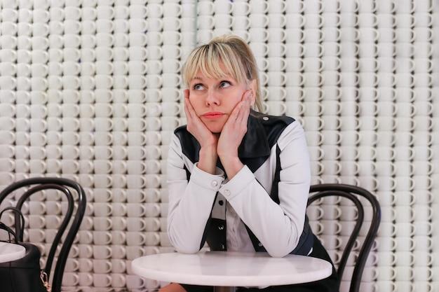 Mooie blonde verveeld alleen in restaurant. het meisje droomt bij lijst in koffiehuis. vrouw zit alleen in café en denkt