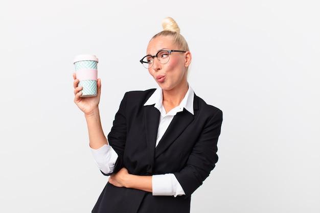 Mooie blonde volwassen zakenvrouw met een koffie om mee te nemen