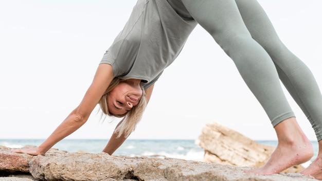 Mooie blonde vrouw beoefenen van yoga op het strand