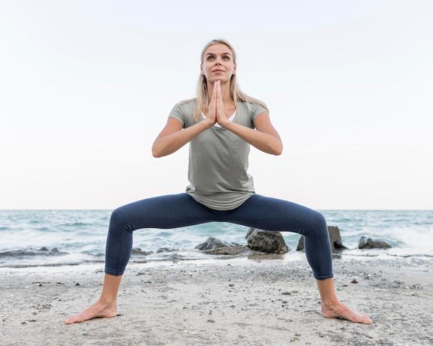 Mooie blonde vrouw buiten het beoefenen van yoga