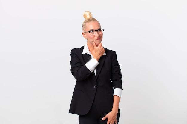 Mooie blonde vrouw denkt, voelt zich twijfelachtig en verward. bedrijfsconcept