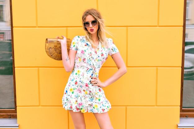 Mooie blonde vrouw die bloemenkleding draagt, die dichtbij gele muur stelt