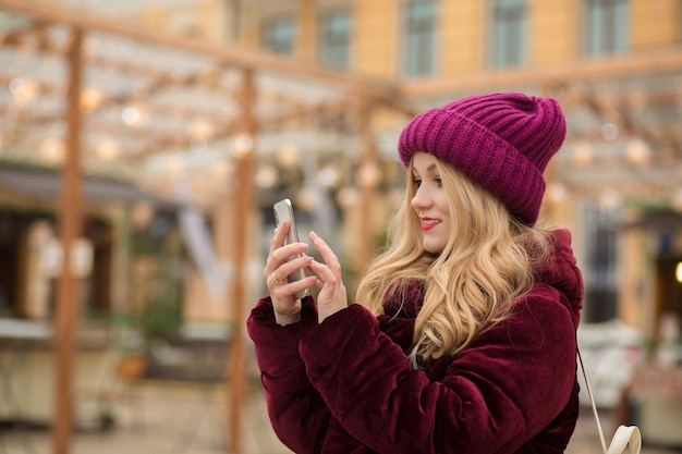 Mooie blonde vrouw die een bericht typt op een mobiele telefoon, staande bij de slinger in kiev