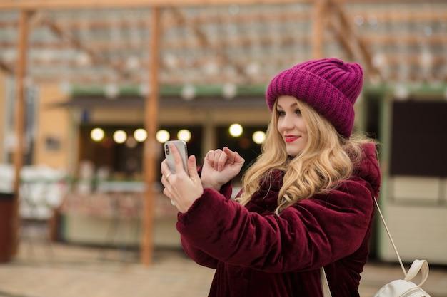 Mooie blonde vrouw die een bericht typt op een mobiele telefoon