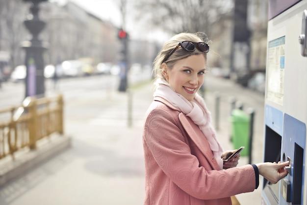 Mooie blonde vrouw die een vervoerskaartje koopt