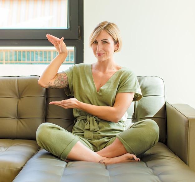 Mooie blonde vrouw die een voorwerp met beide handen vasthoudt, een voorwerp toont, aanbiedt of adverteren