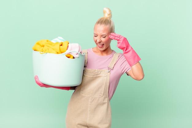 Mooie blonde vrouw die er ongelukkig en gestrest uitziet, zelfmoordgebaar maakt het concept van het wassen van kleding