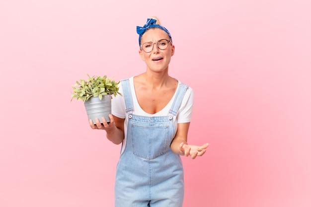 Mooie blonde vrouw die er wanhopig, gefrustreerd en gestrest uitziet en een plant vasthoudt