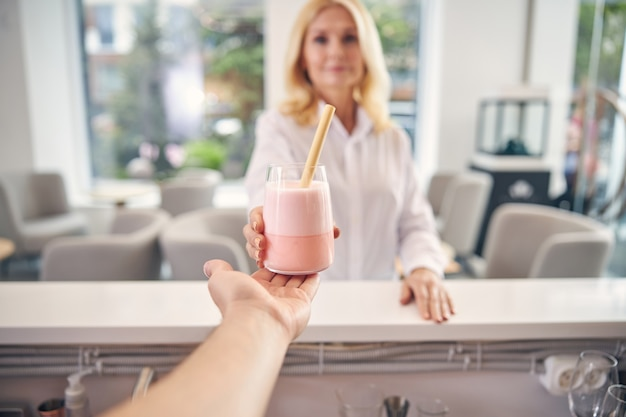 Mooie blonde vrouw die haar hand uitstrekt terwijl ze een cocktail van barmannen neemt