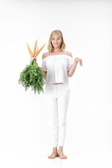 Mooie blonde vrouw die het konijn toont en een verse wortel met groene bladeren op een witte achtergrond houdt. gezondheid en voeding