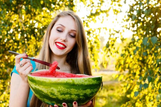 Mooie blonde vrouw die in blauwe kleding een watermeloen in openlucht eet