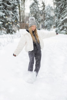 Mooie blonde vrouw die in het bos speelt tijdens de sneeuwval