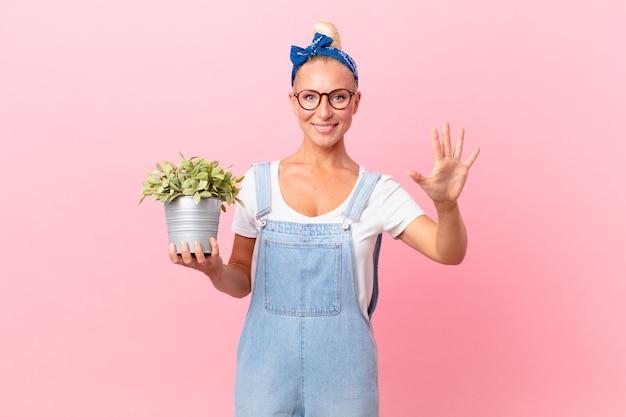 Mooie blonde vrouw die lacht en er vriendelijk uitziet, nummer vijf toont en een plant vasthoudt