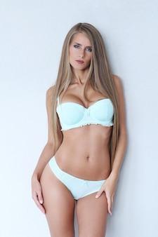 Mooie blonde vrouw die lichtblauwe lingerie draagt
