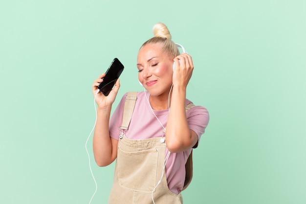 Mooie blonde vrouw die muziek luistert met een koptelefoon