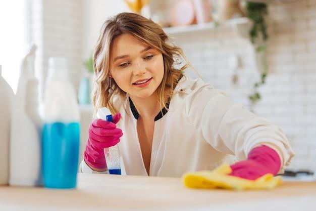 Mooie blonde vrouw die naar het aanrecht kijkt terwijl ze het schoonmaakt