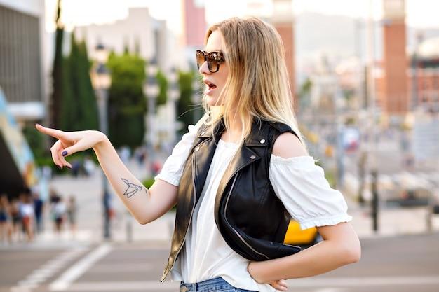 Mooie blonde vrouw die op straat blijft, iets ziet en een verrassend gezicht trekt, trendy modieuze outfit en zonnebril