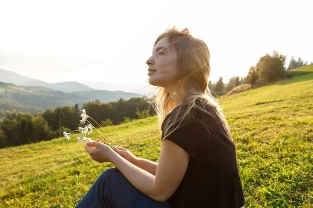 Mooie blonde vrouw die van bergenmening geniet, die camomiles houdt