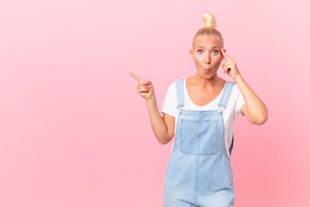 Mooie blonde vrouw die verrast kijkt en een nieuwe gedachte, idee of concept realiseert