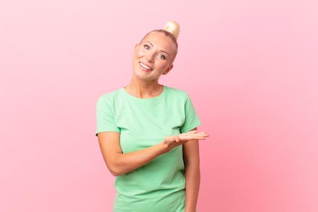 Mooie blonde vrouw die vrolijk lacht, zich gelukkig voelt en een concept toont