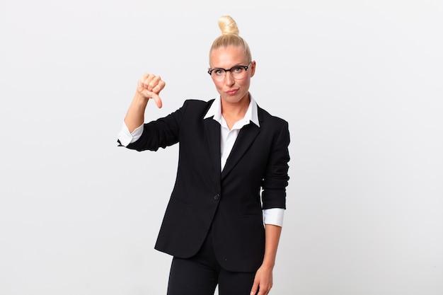 Mooie blonde vrouw die zich boos voelt en duimen naar beneden laat zien. bedrijfsconcept