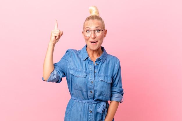 Mooie blonde vrouw die zich een gelukkig en opgewonden genie voelt nadat ze een idee heeft gerealiseerd