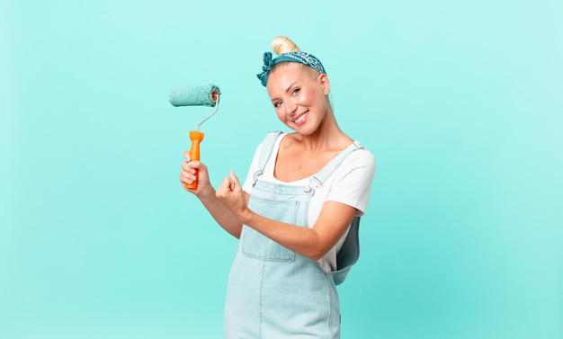 Mooie blonde vrouw die zich gelukkig voelt en een uitdaging aangaat of feest viert en een muur schildert
