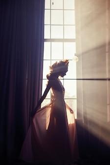 Mooie blonde vrouw die zich in zonlichtvenster bevindt